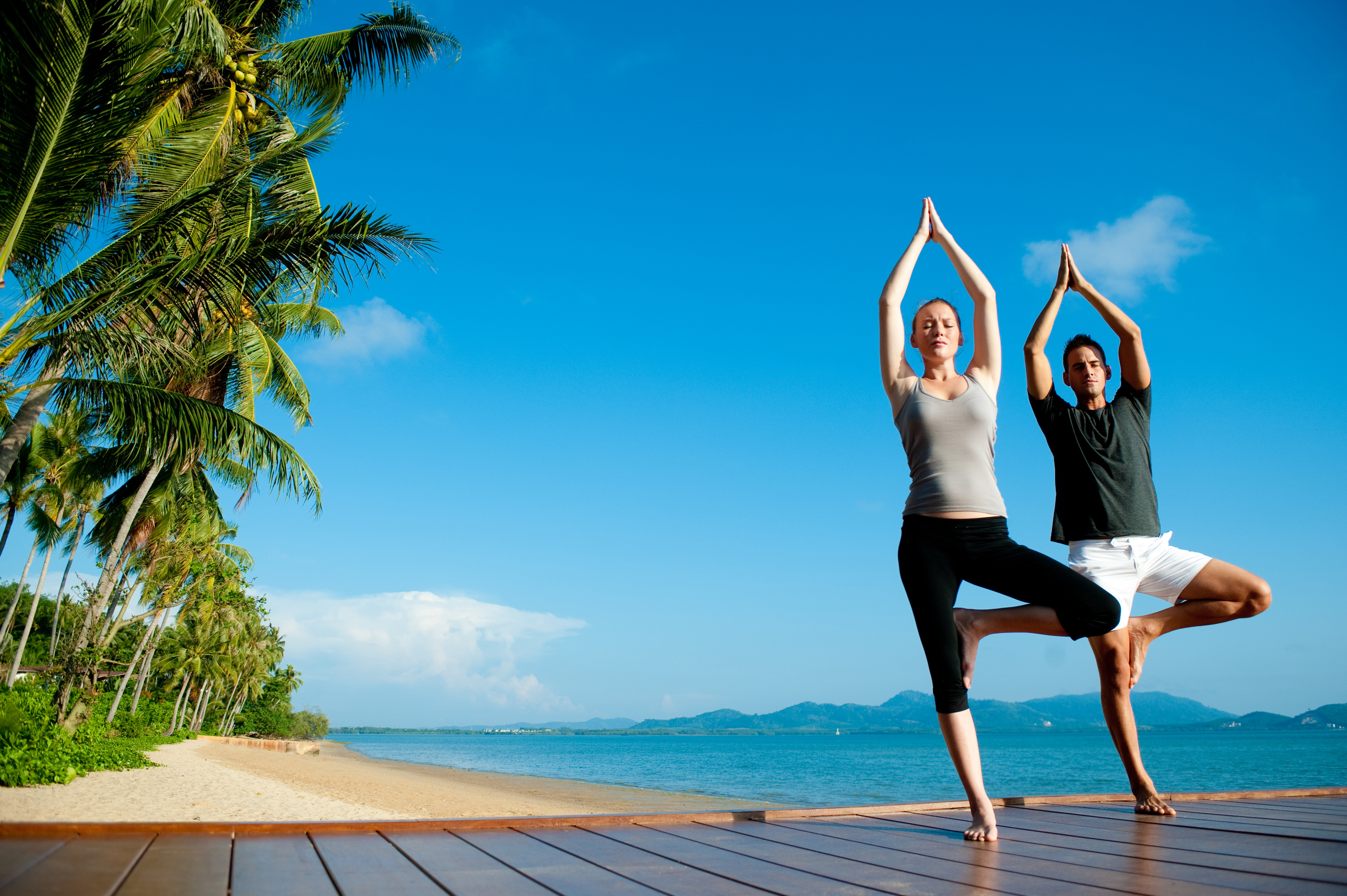 An attractive young woman and man doing yoga on a jetty with the