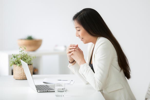 An image of a Woman sitting, Reading from her Computer Screen