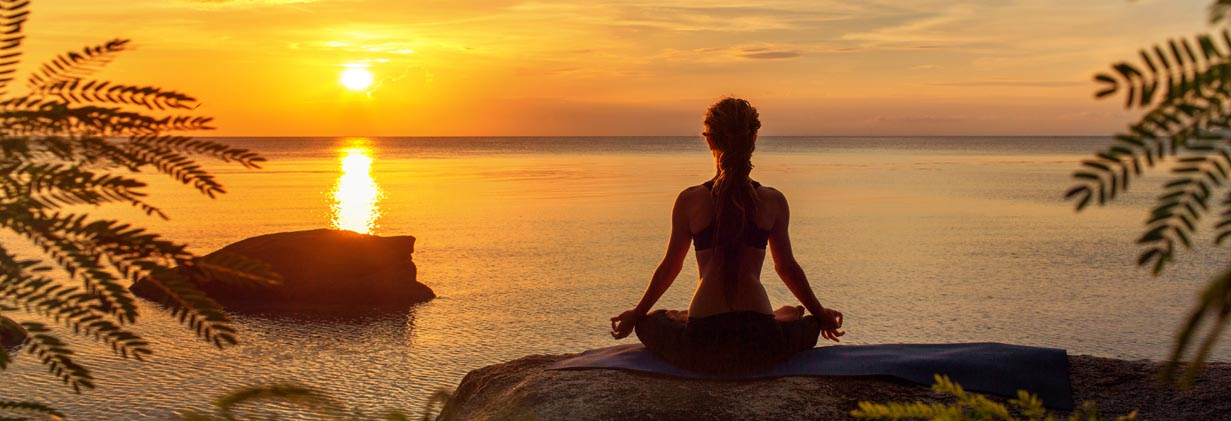 An image of someone meditating overlooking the water and a sunset.